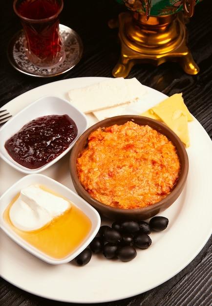 Турецкий завтрак menemen с медом, сливками, оливками, вареньем и сыром вариации в белой тарелке. Бесплатные Фотографии