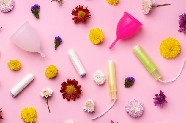 Менструальная чашка и тампоны на вид сверху фон цветочный узор Premium Фотографии