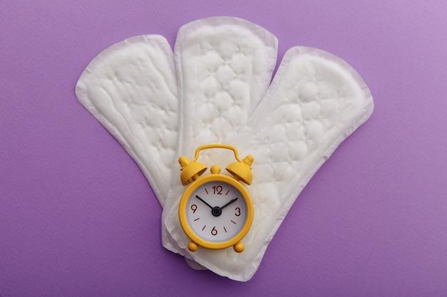 ライラックの背景に月経パッドと黄色の目覚まし時計。女性の月経周期の概念。 Premium写真