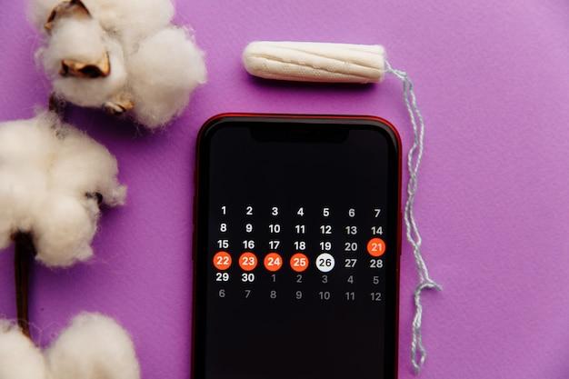 綿とタンポンを使ったスマートフォンの月経カレンダー。女性の重要な日と衛生保護の概念 Premium写真