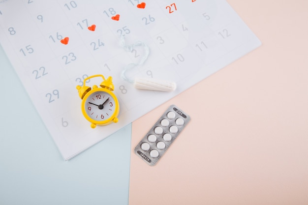 Menstruation calendar with yellow alarm, cotton tampon and contraceptive pills on pink background. woman critical days, woman hygiene protection concept. Premium Photo