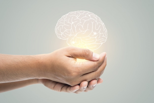 Mental health day. man holding brain illustration on gray wall Premium Photo