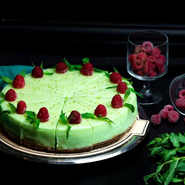 Menthol cheesecake with mint leaves on it and raspberries Free Photo
