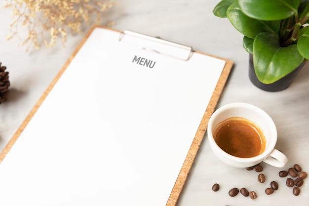入力デザインリストのテキストのためのレストランでのコーヒーカップとメニュー紙モックアップ。 Premium写真