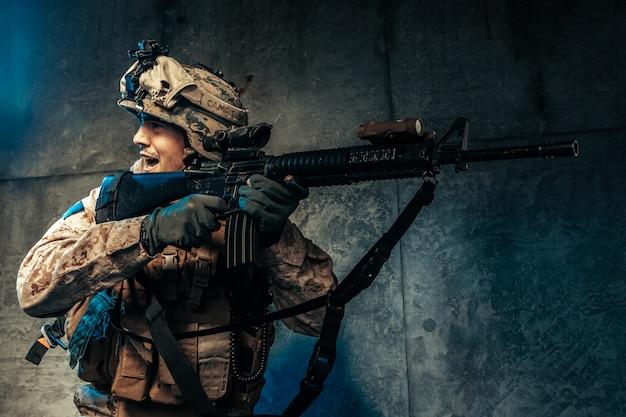 軍服の若い男がスタジオで暗闇の中で現代のmerc兵 Premium写真