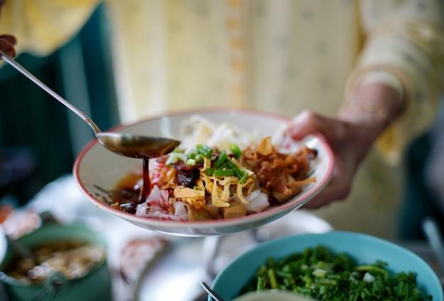 상인은 맛있는 중국 찐 쌀국수 롤 위에 간장을 요리하고 현지 레스토랑에서 고객에게 제공 할 준비가 된 하얀 접시에 아름답게 배열됩니다. 프리미엄 사진