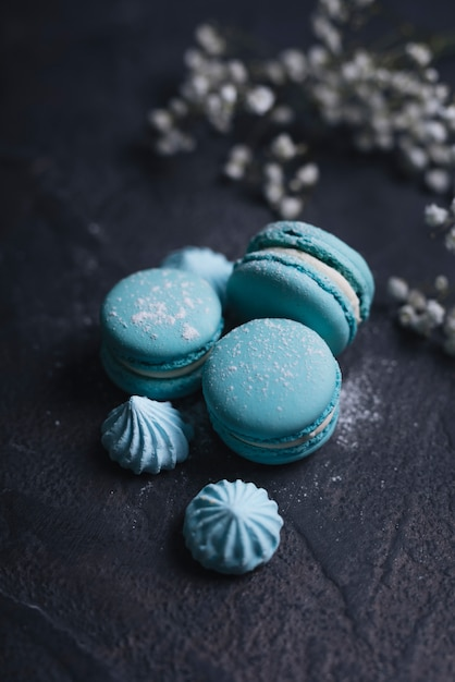 Merengue with stacked of blue macaroon on textured background Free Photo
