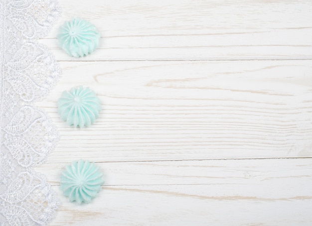 Meringue cookies and white lace on a white wooden background Premium Photo