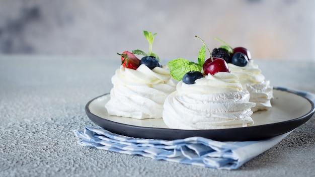 Meringue dessert pavlova cake with fresh berries on a plate. Premium Photo