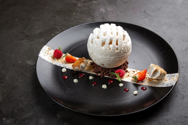 Meringue dessert with raspberries and strawberries in a black plate on a black background Premium Photo