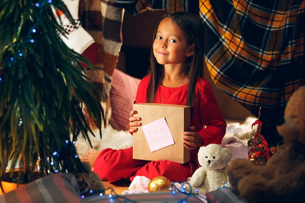 メリークリスマスとハッピーホリデー。かわいい小さな子供の女の子は、屋内の自宅のクリスマスツリーの近くのサンタクロースに手紙を書きます。休日、子供時代、冬、お祝いの概念 無料写真