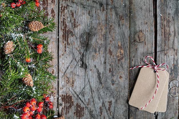 メリークリスマスとハッピーホリデーのグリーティングカード、フレーム、バナー。新年。木製の背景に雪と年賀状。冬のクリスマスの休日のテーマ。フラットレイ。コピースペース 無料写真