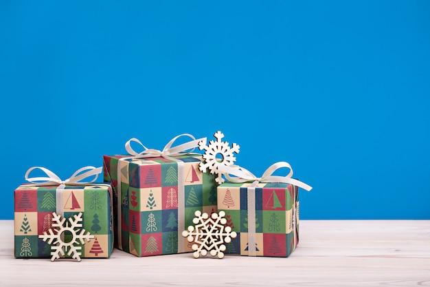 Веселого рождества и счастливого нового года. яркие коробки с лентами и деревянными снежинками на светлом деревянном фоне. Premium Фотографии