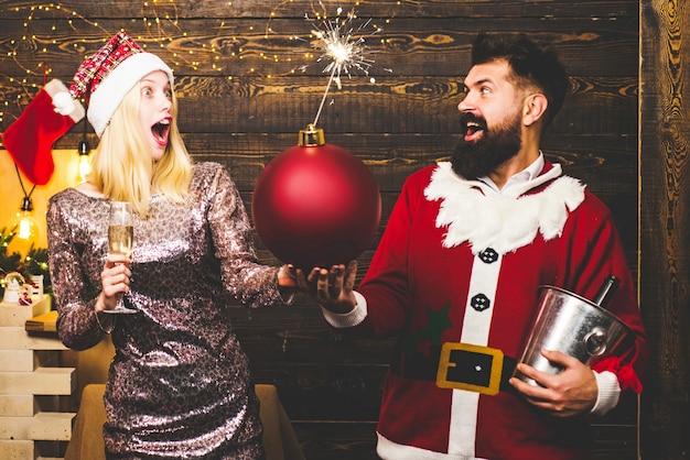 メリークリスマス、そしてハッピーニューイヤー。クリスマスツリーライト上のファッションカップル。官能的 Premium写真