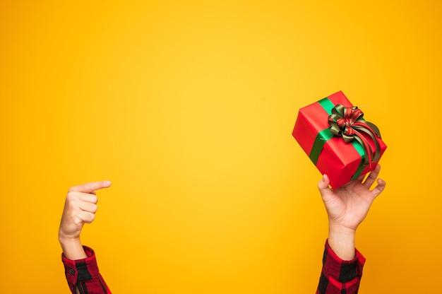 С рождеством и новым годом мужские руки, указывающие на подарочную коробку Premium Фотографии
