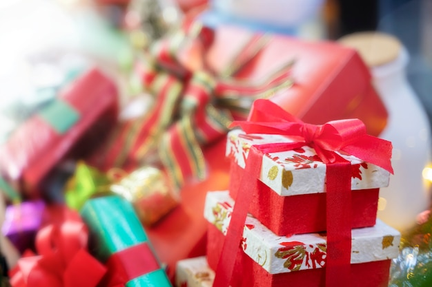 Merry christmas background concept. closeup of red gift box with blurred gift boxes in bac Premium Photo
