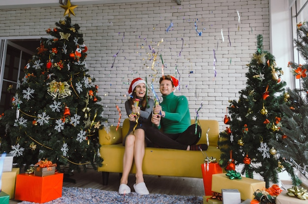 Merry christmas. caucasian sweet couple with red santa hat having fun with colorful christmas tree celebrating in house, holiday family, happy new year and christmas festival concept Premium Photo