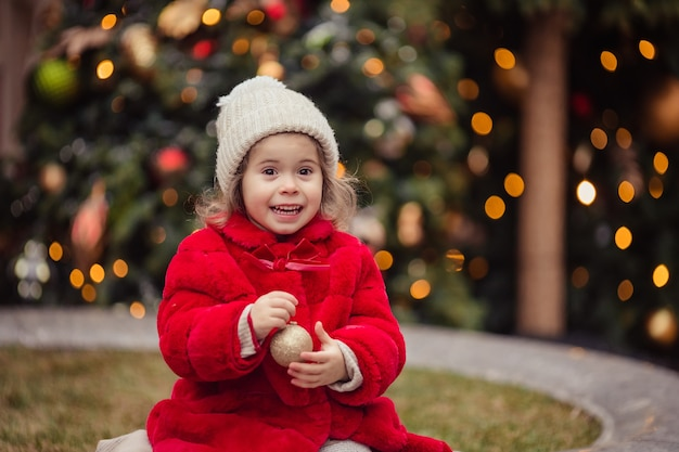 Merry christmas cheerful little girl in a red fur coat at the fair in winter Premium Photo