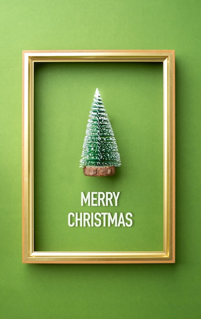 Merry christmas greeting card, green christmas tree with golden frame on green Premium Photo