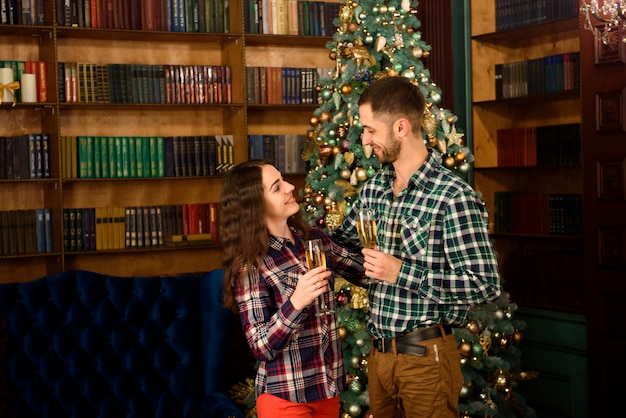 Merry christmas and happy new year! attractive young couple is celebrating holiday at home together, drinking champagne and smiling. Premium Photo