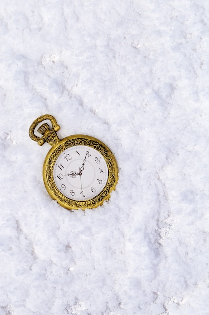 Merry christmas and happy new year greeting card with vintage golden pocket clock on snow background with copy space. Premium Photo