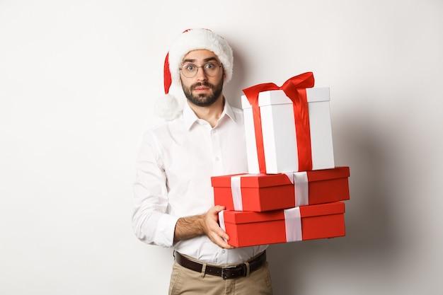 メリークリスマス、休日のコンセプト。プレゼントの山を持っているサンタの帽子の混乱した男は、白い背景に立って、クリスマスツリーの下に贈り物を見つけました。 無料写真