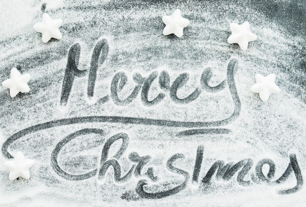 Merry christmas inscription between decorative snow and stars Free Photo