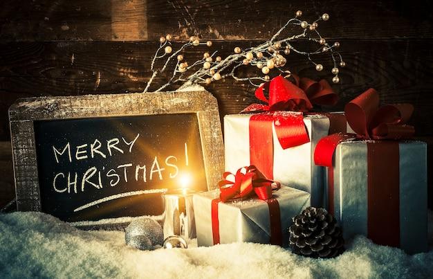 Счастливого рождества на грифельной доске с подарками и свечой. Бесплатные Фотографии