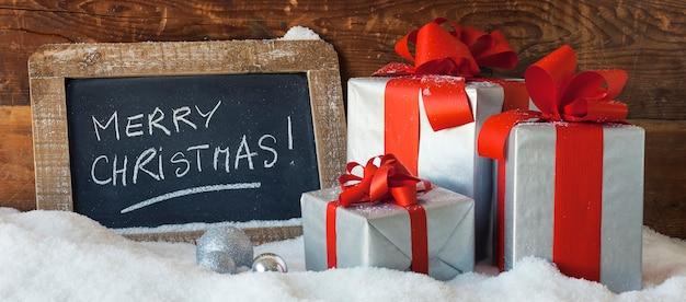 Счастливого рождества на грифельной доске с подарками, панорамный вид. Бесплатные Фотографии