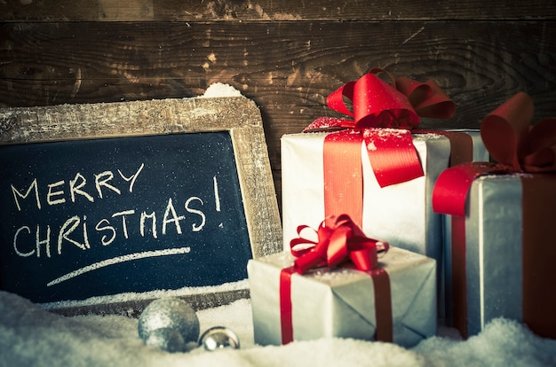 Merry christmas on a slate with gifts. Free Photo