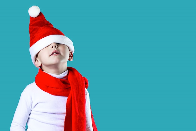 Merry little santa's hat fell down over his eyes. a red scarf is tied around his neck. on a blue background Premium Photo