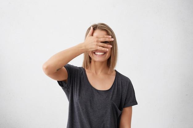 陽気な女性が恥ずかしがり屋の顔を指で覗き見ている。恥ずかしそうに若いかわいい女性がボブの髪型で顔を手で覆い、困惑して広く笑っています。 無料写真