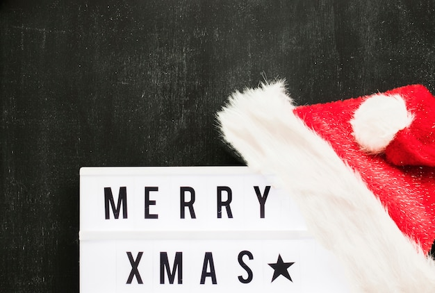 Merry xmas inscription on board with red santa hat Free Photo