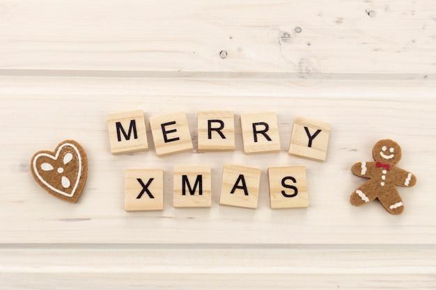 밝은 배경에 진저와 나무 편지 텍스트와 함께 메리 크리스마스 프리미엄 사진