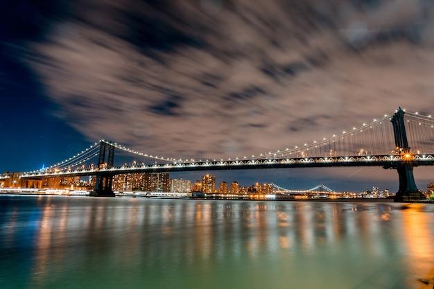 Завораживающая фотография бруклинского моста и огней, отражающихся в воде ночью в сша. Бесплатные Фотографии