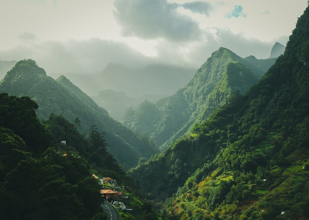 Mesmerizing scenery of green mountains with cloudy sky surface Free Photo