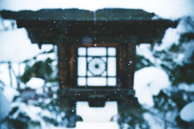 Paesaggio affascinante di neve che cade sopra una lanterna del tempio nel giappone Foto Gratuite