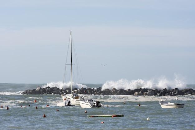 Завораживающий снимок волн за плавучими лодками в дневное время Бесплатные Фотографии