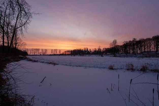 オランダの冬の間に歴史的なドアウォース城の近くの魅惑的な夕日 無料写真