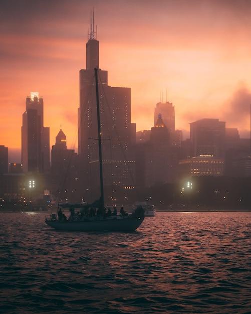 Vista affascinante della barca nell'oceano e le sagome degli edifici alti durante il tramonto Foto Gratuite