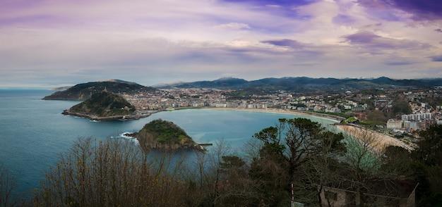 Vista affascinante della città lungo la costa in una giornata nuvolosa con una natura rigogliosa Foto Gratuite