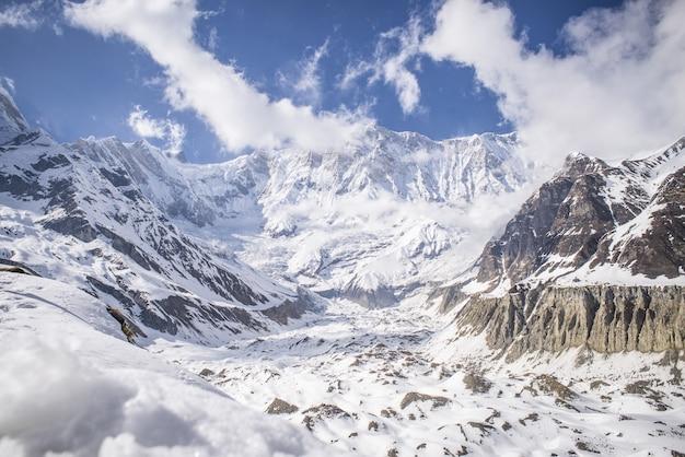 Vista affascinante delle montagne coperte di neve sotto un cielo blu Foto Gratuite