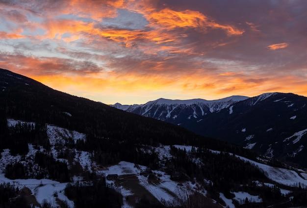 Mesmerizing view of the mountains covered in snow during sunrise Free Photo