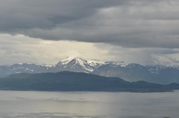 Vista affascinante delle montagne coperte di neve dietro il lago in una giornata uggiosa Foto Gratuite