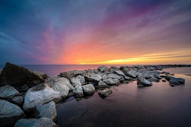 Завораживающий вид на закат над морскими камнями Бесплатные Фотографии