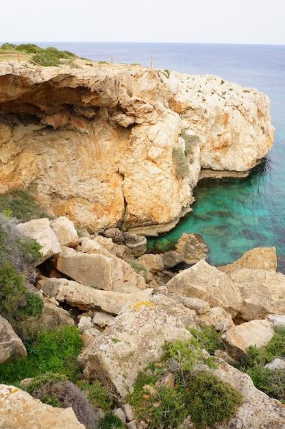 青い空の下の澄んだ海の近くの崖の魅惑的な景色 無料写真