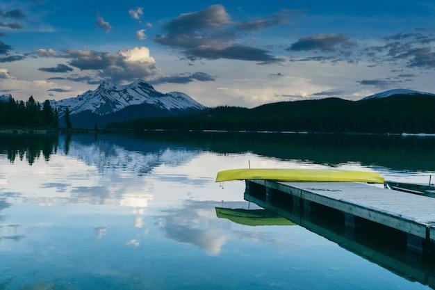 緑豊かな自然と山々に囲まれた湖の近くの桟橋の魅惑的な景色 無料写真
