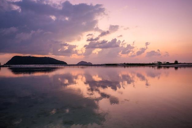 Vista affascinante del cielo che si riflette nell'acqua durante il tramonto Foto Gratuite