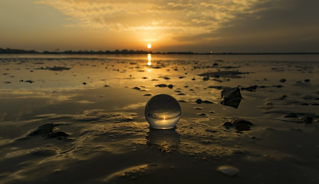 Mesmerizing view of a transparent small ball on the beach captured during the sunset Free Photo