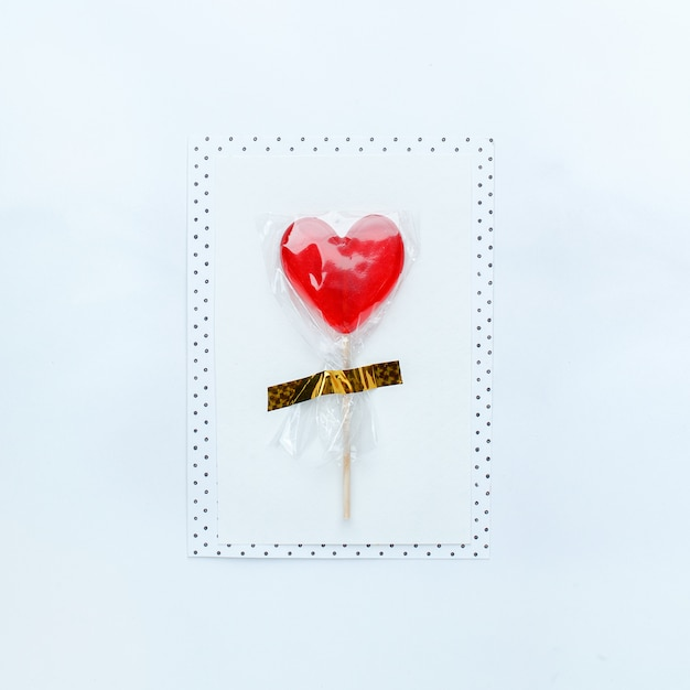 Message card with sugar red heart lollipop on white table  Photo